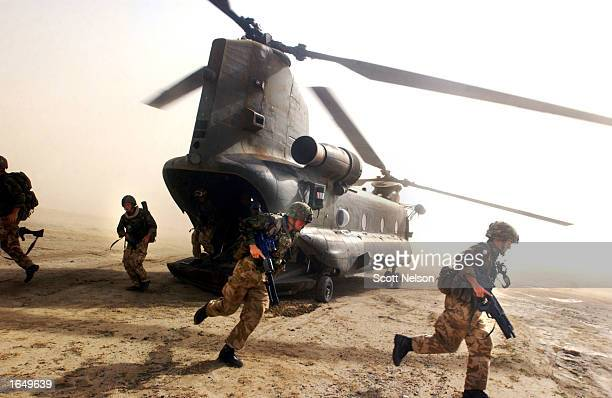 British Royal Marines of 45 Commando scramble out the back of a Chinook helicopter during an eagle vehicle check point operation as part of the...