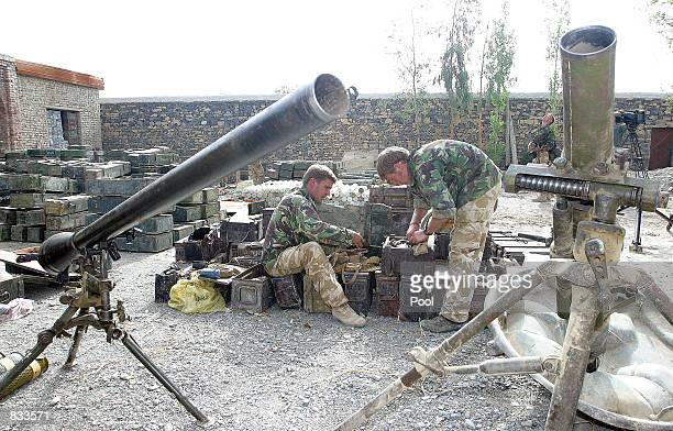 British Royal Marines of 45 Commando sort through a large weapons cache following the discovery of a large weapons and ammo cache June 23 2002 in the...