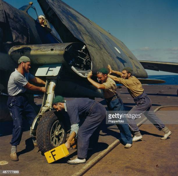 1945 British Royal Navy Aircraft carrier aircrew prepare a carrierborne aircraft for refuelling before action during the Pacific Theatre of World War...