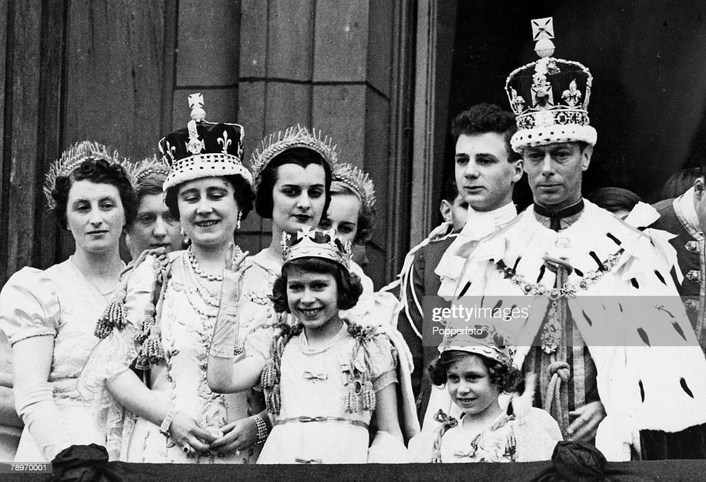 British Royalty, London, England, 12th May 1937, King George VI and Queen Elizabeth pictured wearing their crowns and coronation robes as they stand on the balcony of Buckingham Palace with Princess Elizabeth (waving) and Princess Margaret