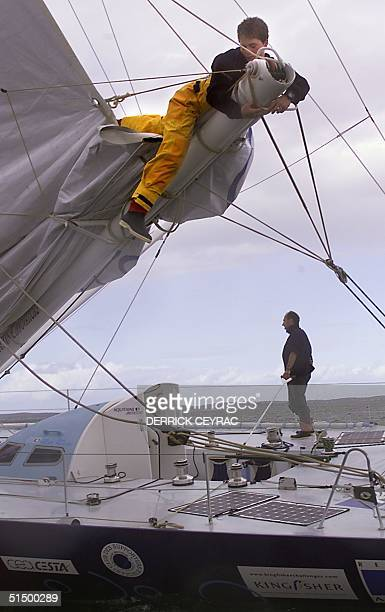 British sailor Ellen MacArthur a member of Frenchman Yves Parlier's crew on the 'Acquitaine Innovations' frees a stuck mainsail rope on the boom as...