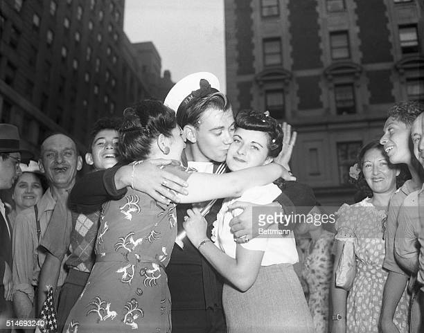 British sailor Ray Bradley celebrates VJ Day in New York City with kisses from two American girls