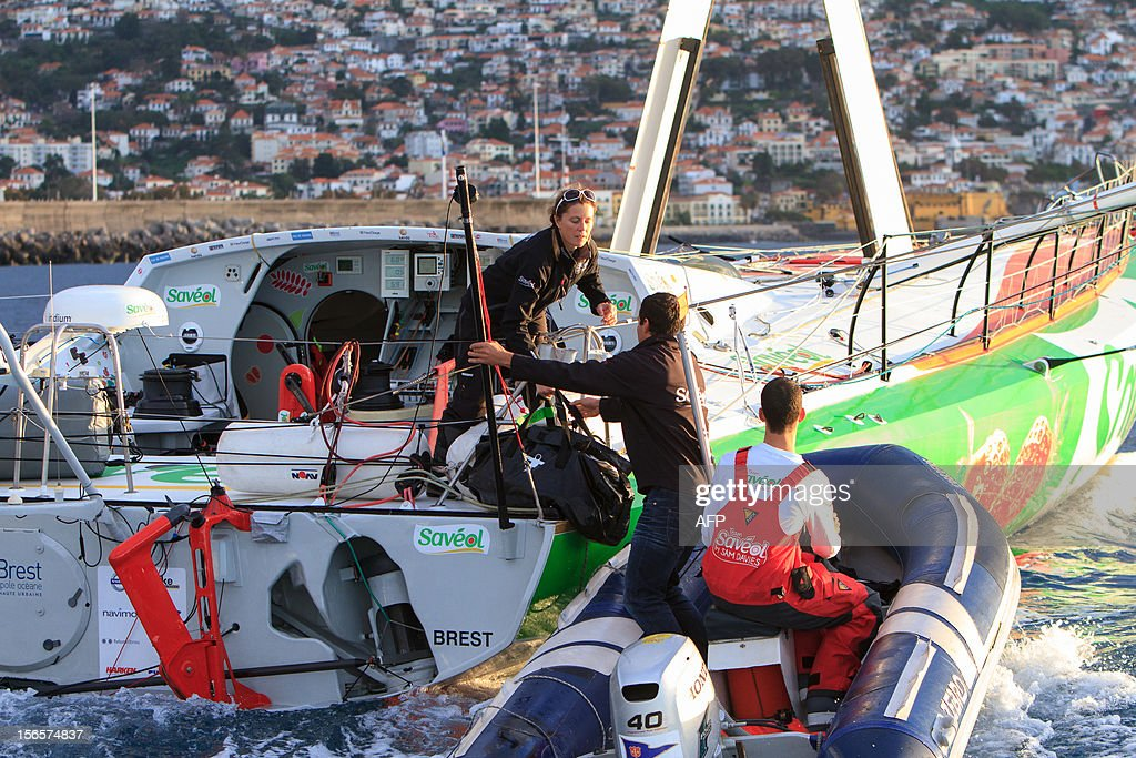 British sailor Samantha Davies (L) helps her partner Romain Attanasio (C) to join her on board as she arrives on November 17, 2012 in Funchal, on the island of Madeira, Portugal. Davies, who was eliminated from the solo, round-the-world Vendee Globe after the dismasting of her yacht, limped into Madeira on November 17. The 38-year-old, the only woman in the world's most gruelling yacht race, saw her boat dismasted on Thursday evening in strong winds about 130 nautical miles northeast of Madeira, the Portuguese island in the Atlantic Ocean.