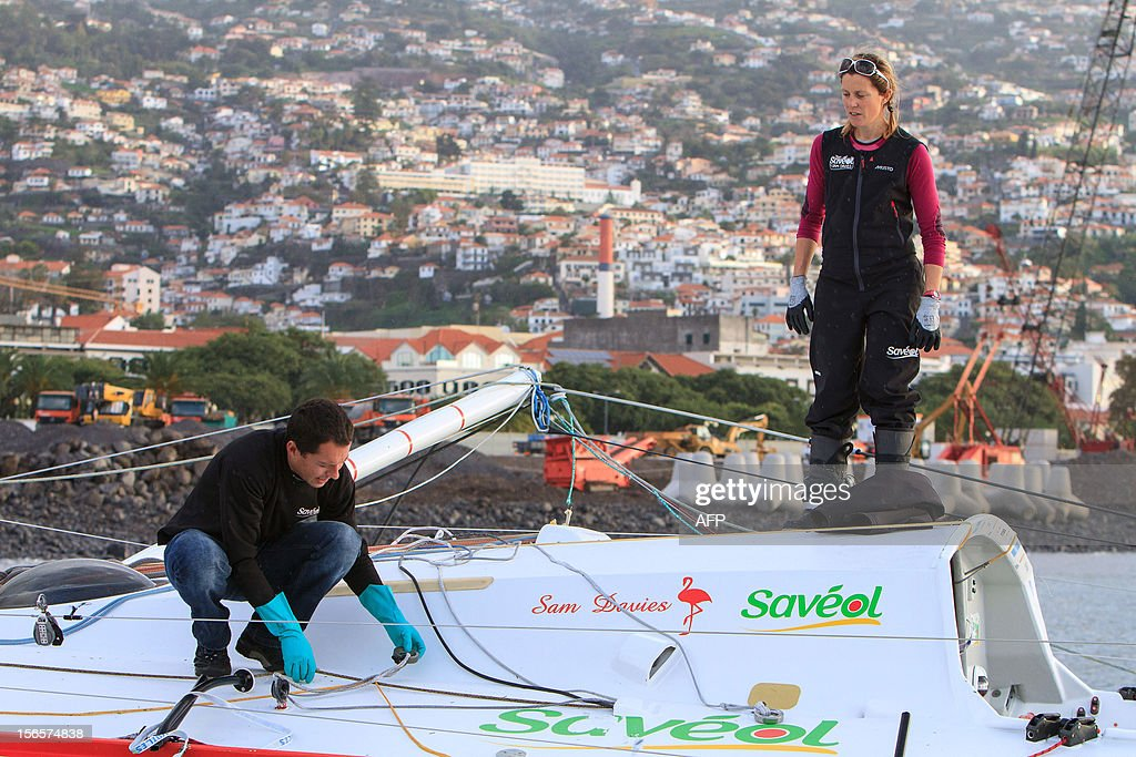 British sailor Samantha Davies (R) looks at her partner Romain Attanasio who joined her on board as she arrives on November 17, 2012 in Funchal, on the island of Madeira, Portugal. Davies, who was eliminated from the solo, round-the-world Vendee Globe after the dismasting of her yacht, limped into Madeira on November 17. The 38-year-old, the only woman in the world's most gruelling yacht race, saw her boat dismasted on Thursday evening in strong winds about 130 nautical miles northeast of Madeira, the Portuguese island in the Atlantic Ocean. AFP PHOTO / GREGORIO CUNHA
