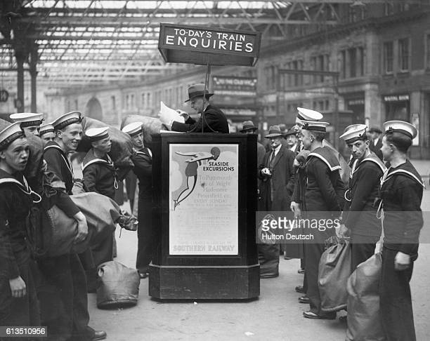 British sailors about to return to their ships talking to the customer service representative at Waterloo Station in London 1934