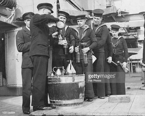 British sailors of the 'HMS Curacoa' receive their rum ration at sea 1940