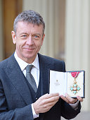 British screenwriter Peter Morgan holds his medal after being appointed a Commander of the Order of the British Empire at an investiture ceremony at...