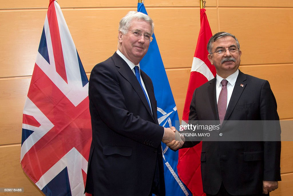 British Secretary of State for Defense Michael Fallon (L) shakes hands with Turkish Defense Minister Ismet Yilmaz prior to a meeting at NATO headquarters in Brusselson February 11, 2016. NATO defense ministers met for a second day on Thursday to discuss Turkeys request to help deal with Europes ongoing migrant crisis and the current situation in Iraq and Syria. / AFP / POOL / Virginia Mayo