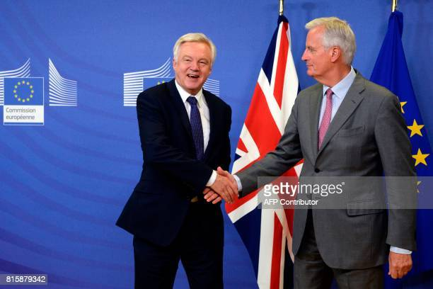 British Secretary of State for Exiting the European Union David Davis shakes hands with European Union Chief Negotiator in charge of Brexit...