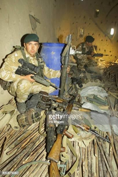 British servicemen Second Lieutenant David Spink and Corporal John Andrews examine arms found at a mudbrick barn in Atalay village 50 miles northwest...