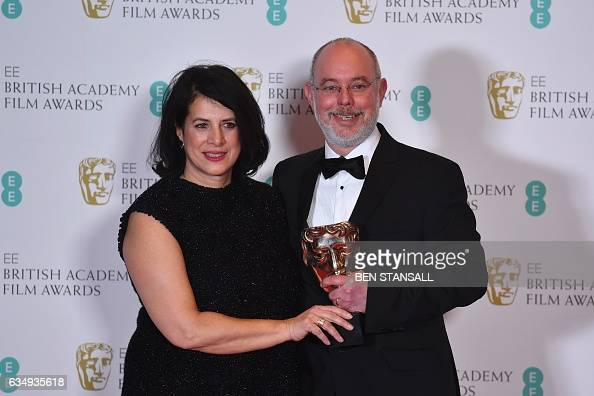 British set decorator Anna Pinnock and art director James Hambidge pose with the award for Production Design for the film 'Fantastic Beasts And Where...