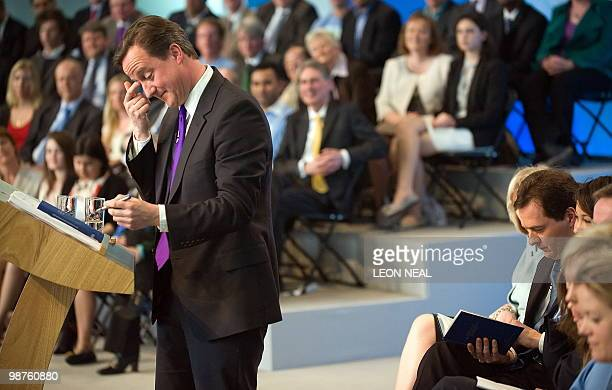 British Shadow Chancellor George Osborne reads the newly launched Conservative election manifesto as party leader David Cameron addresses supporters...