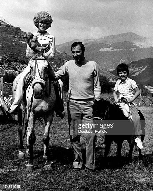 British showgirl Minnie Minoprio on a horse with a dog in her arms smiling Her Italian husband Giorgio Ammanniti and her Italian son Giuliano...