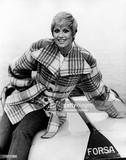 British showgirl Minnie Minoprio posing smiling in a tartan coat Ligano 1970s
