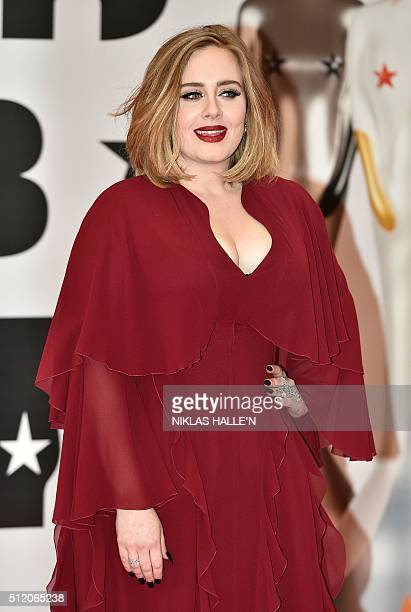 British singer Adele poses on the red carpet after arriving to attend the BRIT Awards 2016 in London on February 24 2016 / AFP / NIKLAS HALLE'N /...