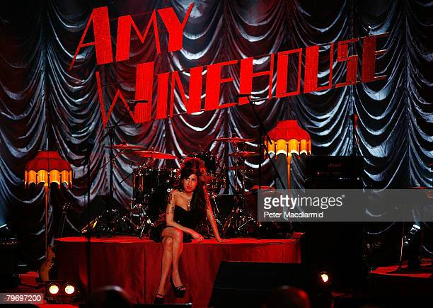 British singer Amy Winehouse sits on stage and looks up at a television monitor whilst awaiting news of her Grammy Award at The Riverside Studios for...