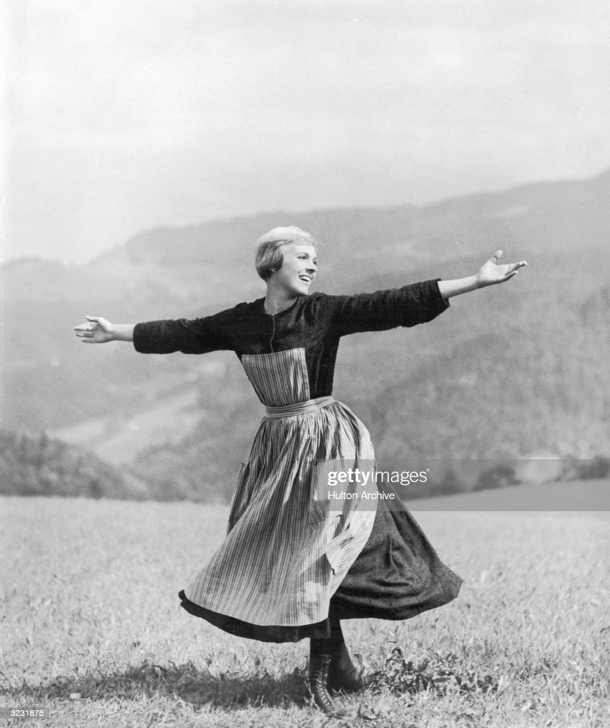British singer and actress Julie Andrews twirls while singing on top of a mountain in the opening scene of director Robert Wise's film, 'The Sound of Music'.
