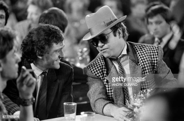 British singer and musician Elton John speaks with French football player Michel Platini on December 17 1984 in Paris / AFP PHOTO / Philippe WOJAZER