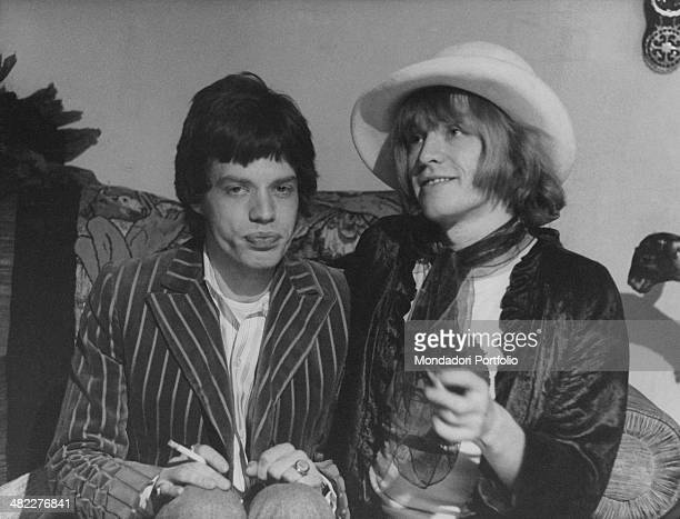 British singer and musician Mick Jagger sitting beside British guitarist and multiinstrumentalist Brian Jones wearing woman clothes The two are...