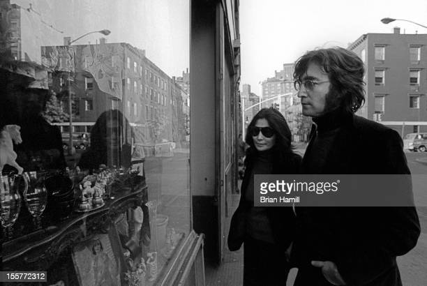 British singer and songwriter John Lennon and his wife Japaneseborn musician and artist Yoko Ono look in a window display in their neighborhood...