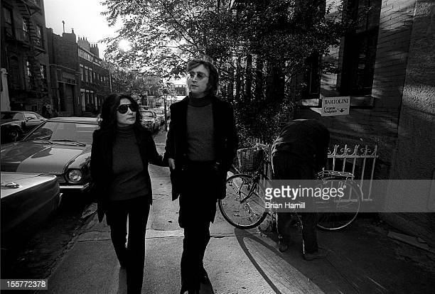 British singer and songwriter John Lennon and his wife Japaneseborn musician and artist Yoko Ono stroll around their neighborhood around Bank Street...