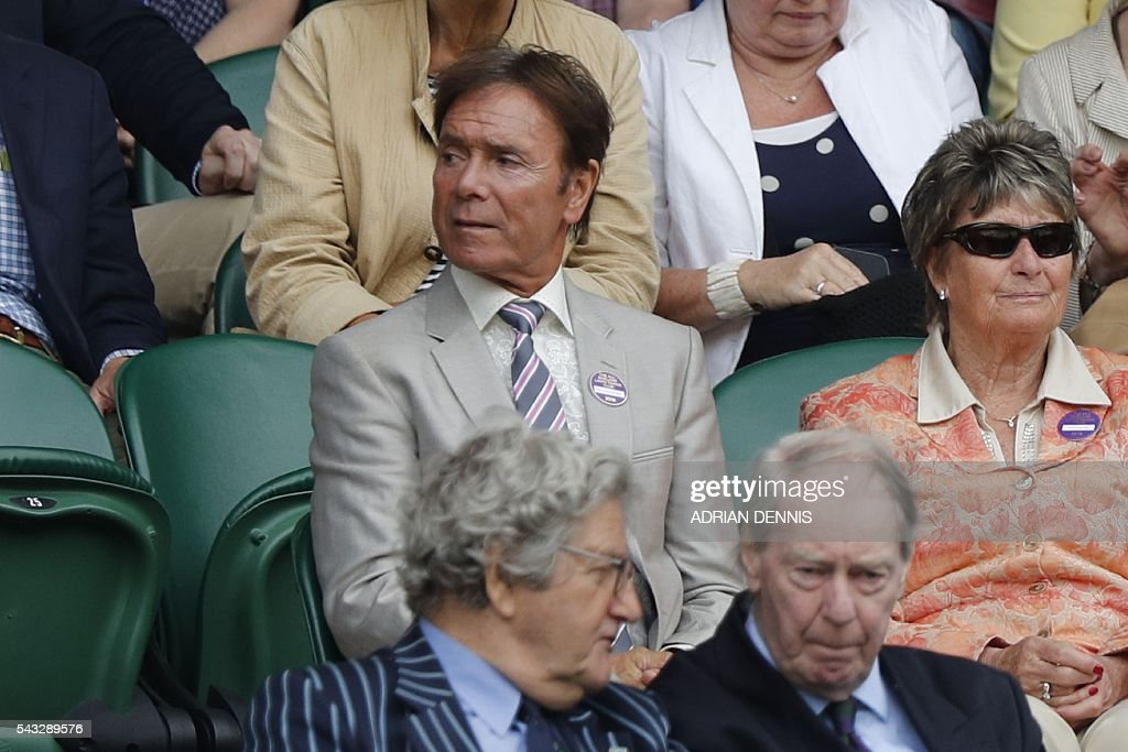British singer Cliff Richard (C) watches Serbia's Novak Djokovic play against Britain's James Ward during their men's singles first round match on the first day of the 2016 Wimbledon Championships at The All England Lawn Tennis Club in Wimbledon, southwest London, on June 27, 2016. / AFP / ADRIAN