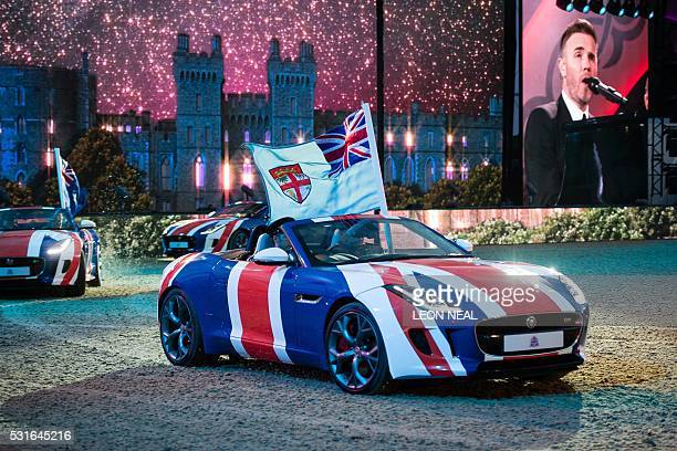 TOPSHOT British singer Gary Barlow performs as Jaguar sports cars drive around the arena during the final night of The Queen's 90th Birthday...