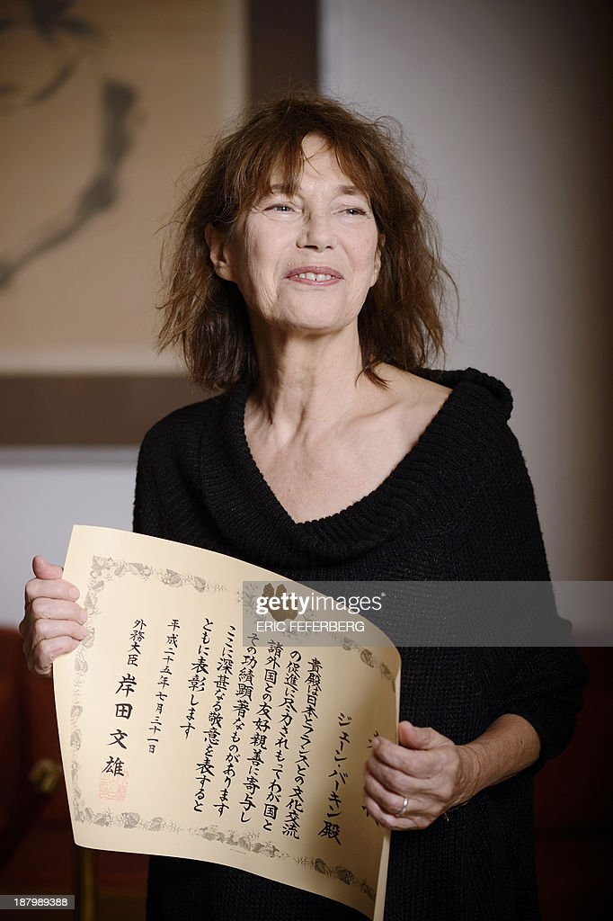 British singer Jane Birkin displays a diploma she received from japanese foreign minister for her support to Japan after the tsunami and the nuclear accident in 2011 on November 14, 2013 at the Japan embassy in Paris.