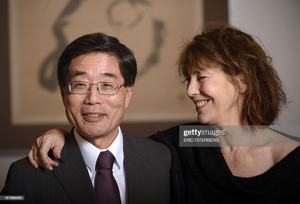 British singer Jane Birkin (R) poses with Japanese ambassador to France Ichiro Komatsu after she received a diploma for her support to Japan after the tsunami and the nuclear accident in 2011 on November 14, 2013 in Paris. AFP PHOTO ERIC FEFERBERG
