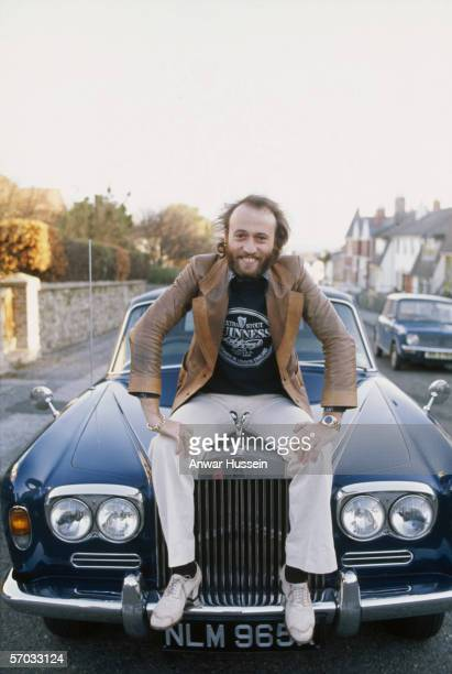 British singer Maurice Gibb of the Bee Gees poses on the bonnet of his RollsRoyce circa 1975