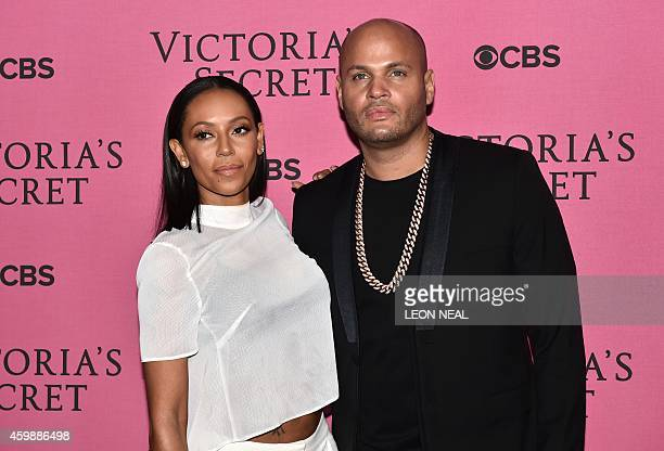British singer Melanie Brown and her husband Stephen Belafonte poses for pictures on the pink carpet with an unidentified guest upon arrival for the...