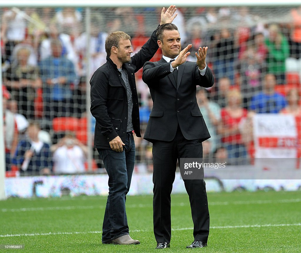 British singer Robbie Williams (R) and former 'Take That' band mate Garry Barlow gesture as they pose on the pitch before the Unicef Soccer Aid charity football match at Old Trafford in Manchester, north-west England on June 6, 2010. Soccer Aid is the brainchild of Robbie Williams and all money raised through profits from ticket sales and donations made by viewers of ITV during the match will go to UNICEF�s invaluable work helping children around the world.