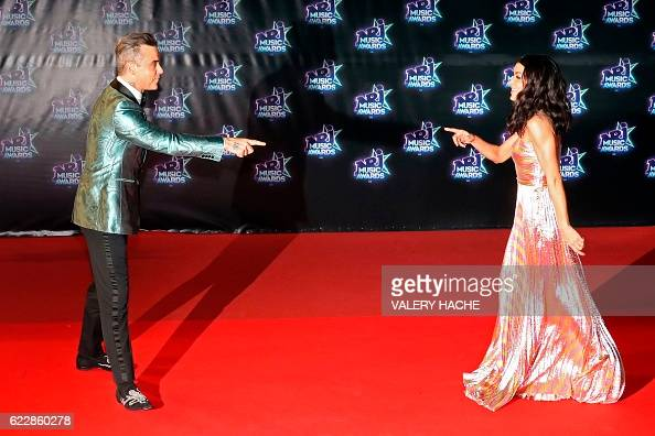 TOPSHOT British singer Robbie Williams and French singer Jennifer gesture on the red carpet upon their arrival to the 18th Annual NRJ Music Awards on...