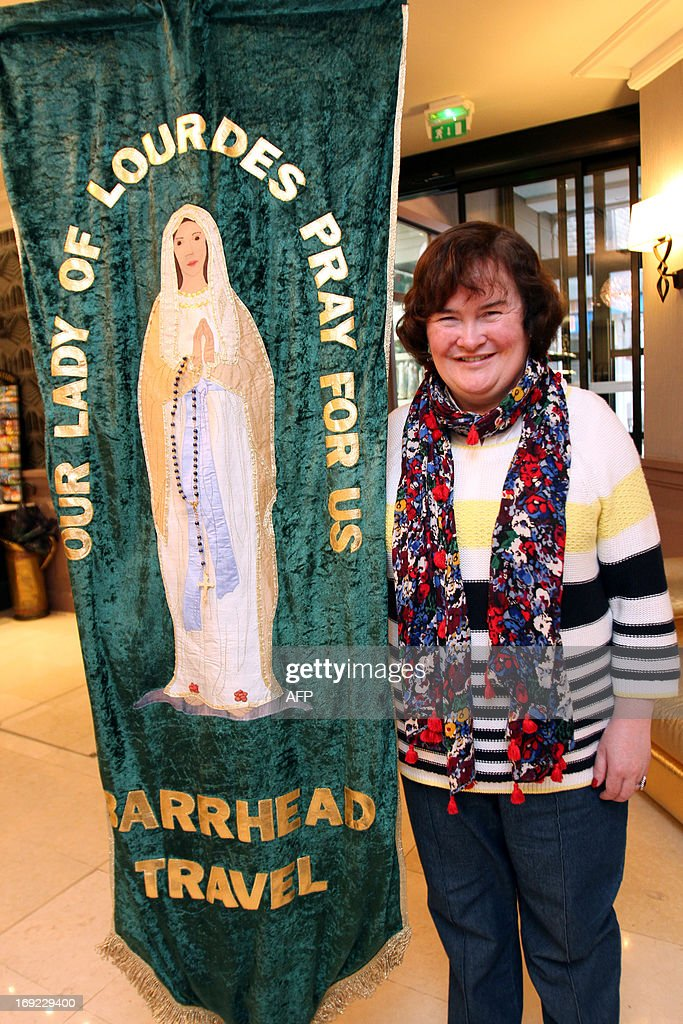 British singer Susan Boyle holds a banner with an image of the Virgin Mary as she poses for a photograph in a hotel during her pilgrimage to the city of Lourdes, on May 21, 2013. AFP PHOTO / LAURENT DARD