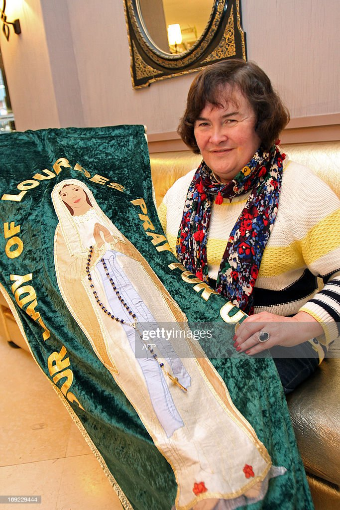 British singer Susan Boyle holds a banner with an image of the Virgin Mary as she poses for a photograph in a hotel during her pilgrimage to the city of Lourdes, on May 21, 2013.