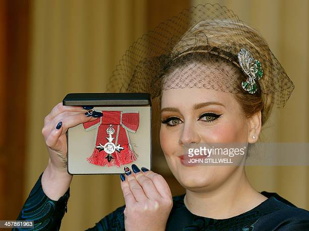 British singersongwriter Adele Adkins holds her medal after being appointed a Member of the Order of the British Empire for services to music...
