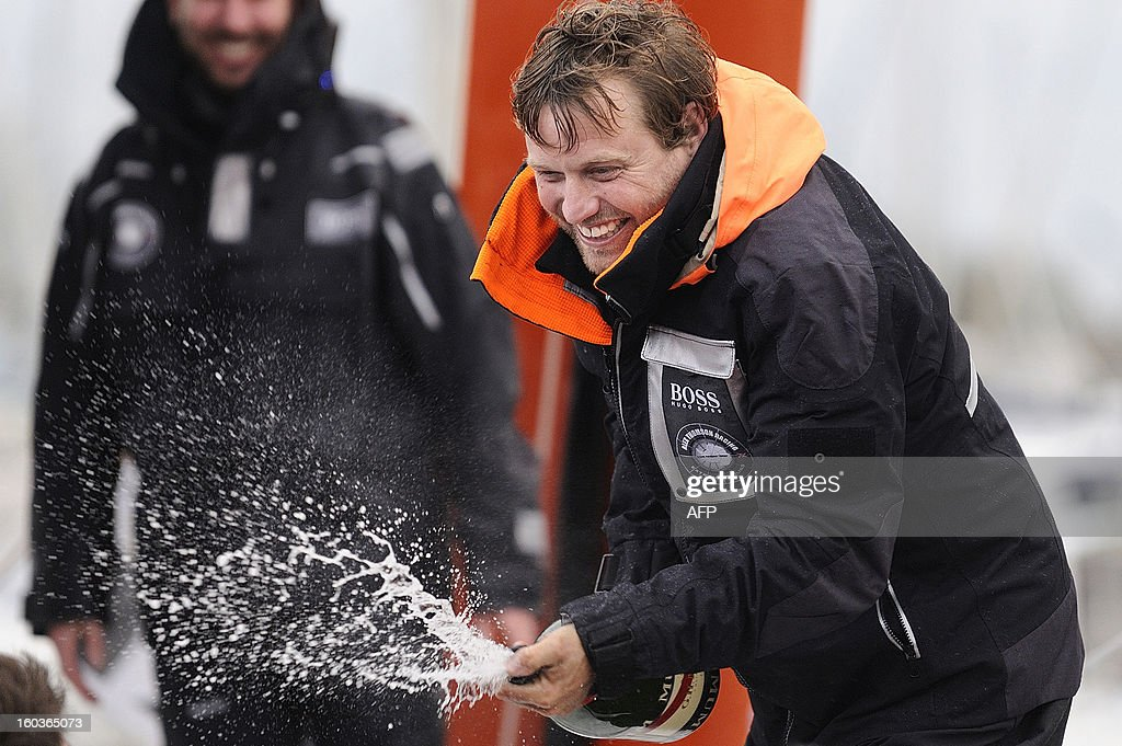 British skipper Alex Thomson sprays champagne on his monohull 'Hugo Boss' placing third in the 7th edition of the Vendee Globe solo round-the-world race on January 30, 2013 in Les Sables d'Olonne, western France.