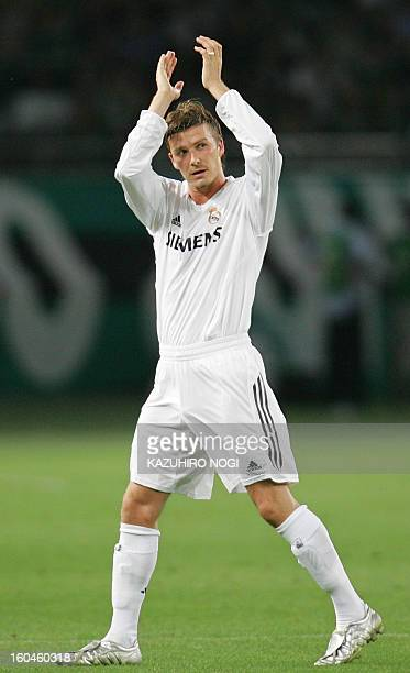 British soccer player David Beckham of Real Madrid acknowledges the applause from cheering Japanese fans as he leaves the field during a friendly...
