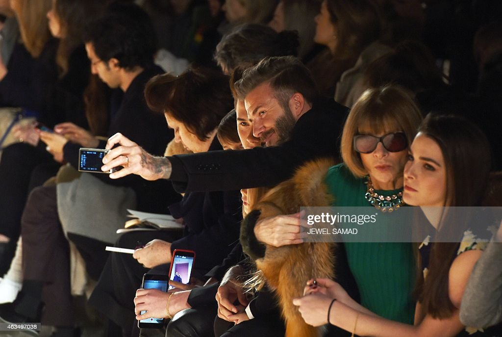 British soccer player David Beckham (C) takes a selfie with his children as he attends a fashion show by his wife and designer Victoria Beckham during the Mercedes-Benz Fashion Week Fall 2015 in New York on February 15, 2015.