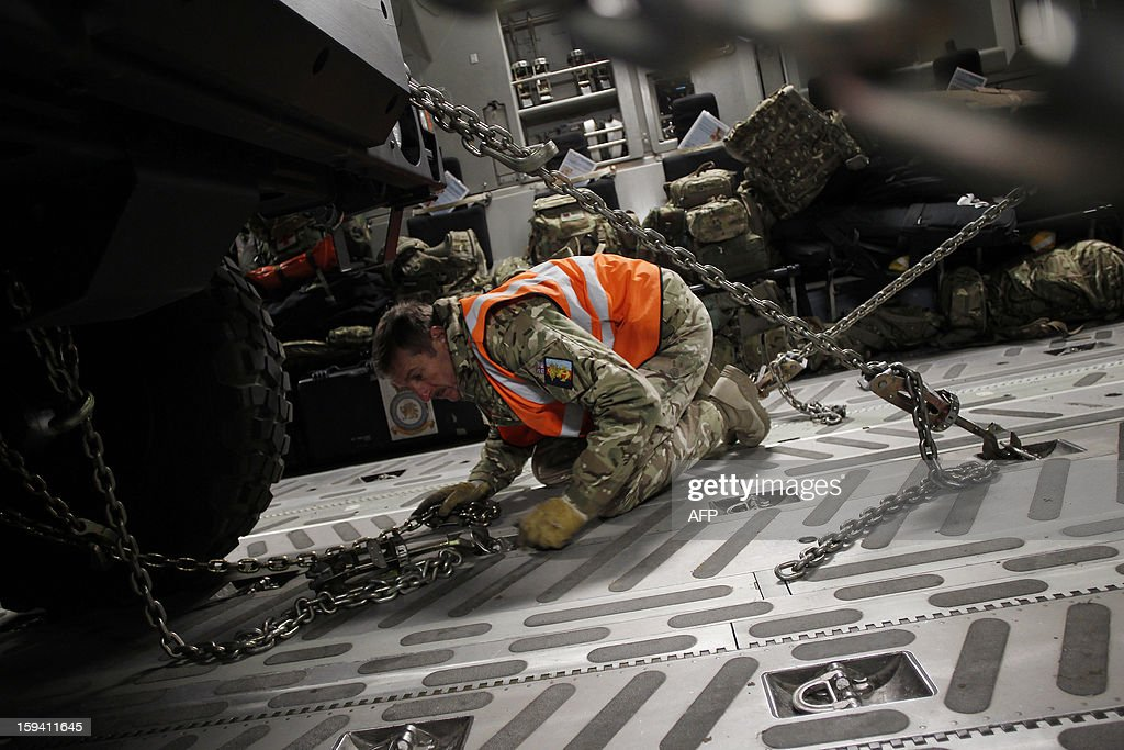 A British soldier adjusts chains to a French armoured vehicle load with other material in a British army Boeing C-17 cargo aircraft arriving from British Brize Norton base en route to Bamako, on January 13, 2013 at the Evreux military Base. Britain supports France's decision to send troops to support an offensive by Mali government forces against Islamist rebels.