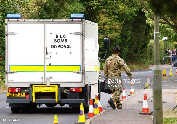 A British soldier from the bomb disposal squad prepares to enter the house of a British family shot dead in the French Alps in Claygate in southeast...