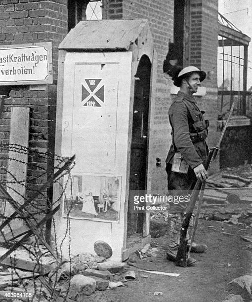 A British soldier on sentry duty after the fall of Peronne France First World War Someone has pasted a picture of the British royal family to the...