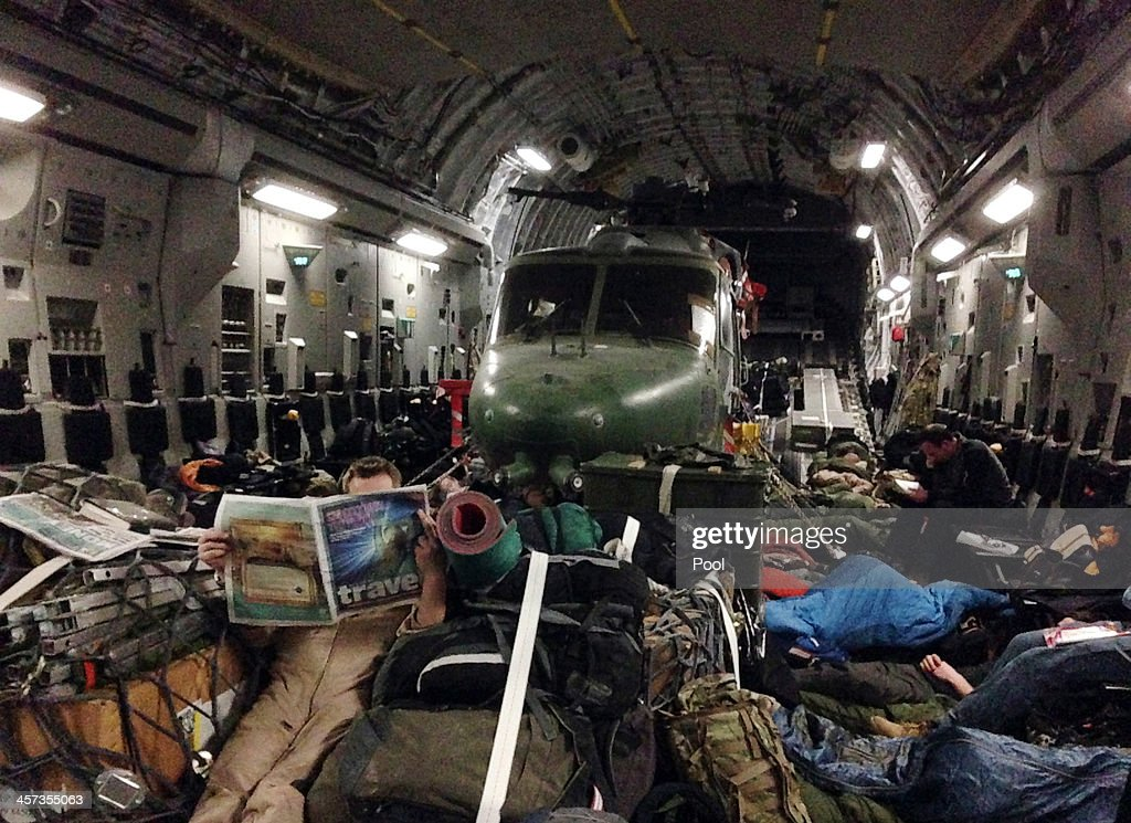 British soldier reads a newspaper as he rests aboard a Royal Air Force transport aircraft on its way back to Britain from Camp Bastion on December 16...