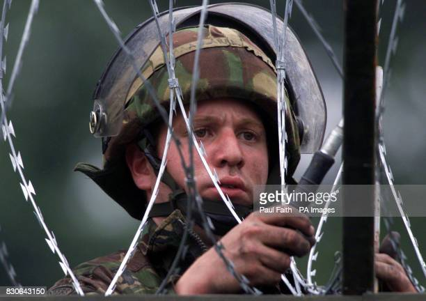 A British soldier secures razor wire to the top of the steel barricade on Drumcree Bridge Security forces have sealed off fields and roads opposite...