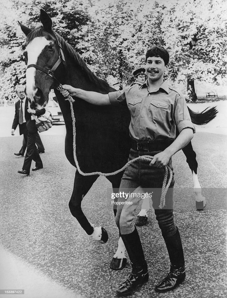 British soldier Sergeant Michael Pedersen, of the Blues and Royals cavalry regiment, leading his horse Sefton, circa 1983. Pedersen was riding Sefton in a military parade in Hyde Park on 20th July 1982, when a Provisional IRA car bomb killed five soldiers and seven horses. Sefton survived despite a severed jugular vein, an eye injury and 34 other wounds.
