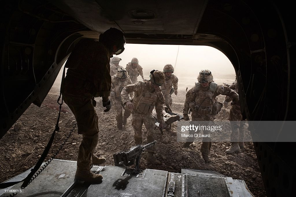 British soldiers carry on a stretcher into the British Royal Air Force MERT CH47 Chinook helicopter two fellows British soldiers on November 26 2009...