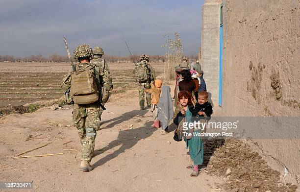 British soldiers from the Yorkshire Regiment pass by local children on route to a patrol base in the village of Khar Nikah in Nahre Saraj district...