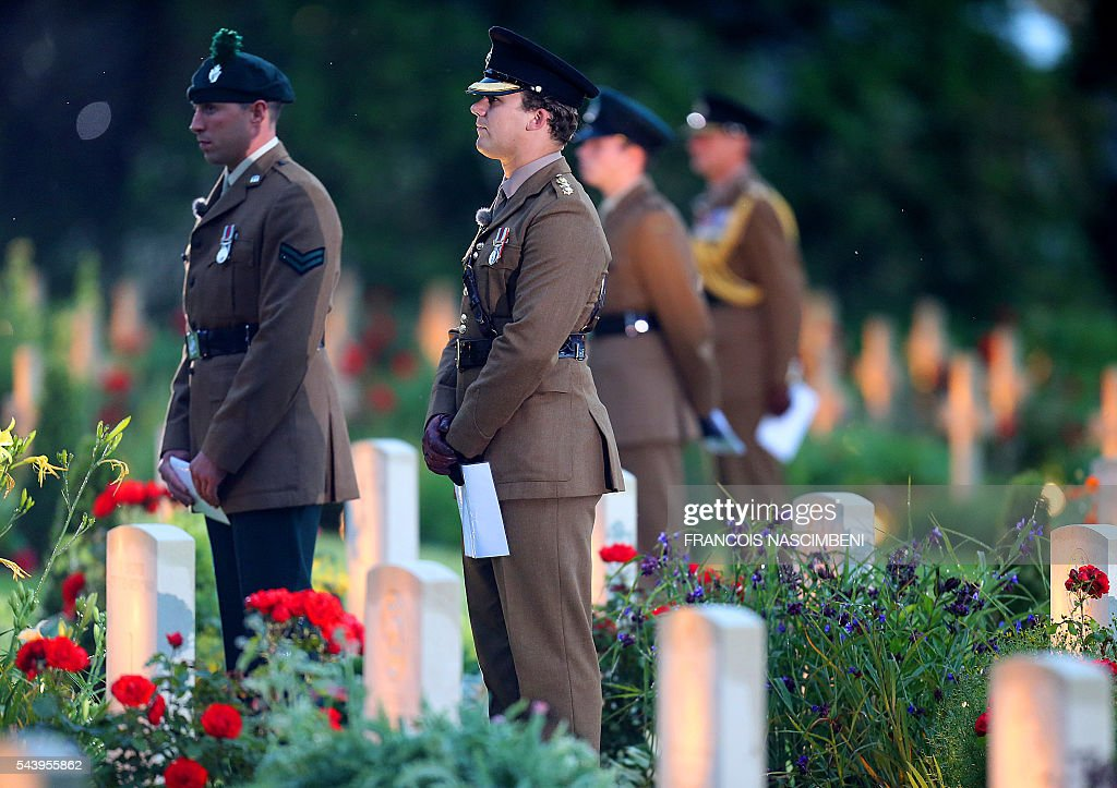 British soldiers stand among lighted WWI British soldiers graves during a ceremony to commemorate the centenary of the battle of the Somme, one of the deadliest of the World War I (1.2 million killed, missing and wounded in five months), on June 30, 2016 at the memorial of Thiepval, northern France. / AFP / FRANCOIS