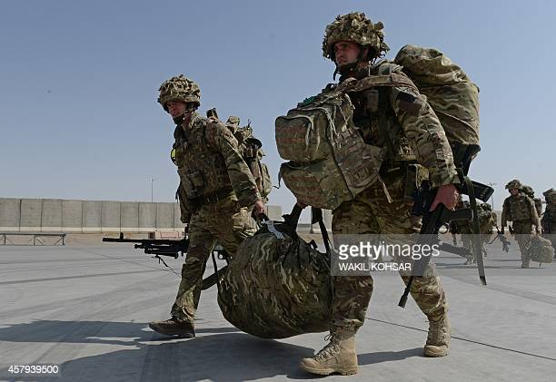 British soldiers walk with their gear after arriving in Kandahar on October 27 as British and US forces withdraw from the Camp BastionLeatherneck...