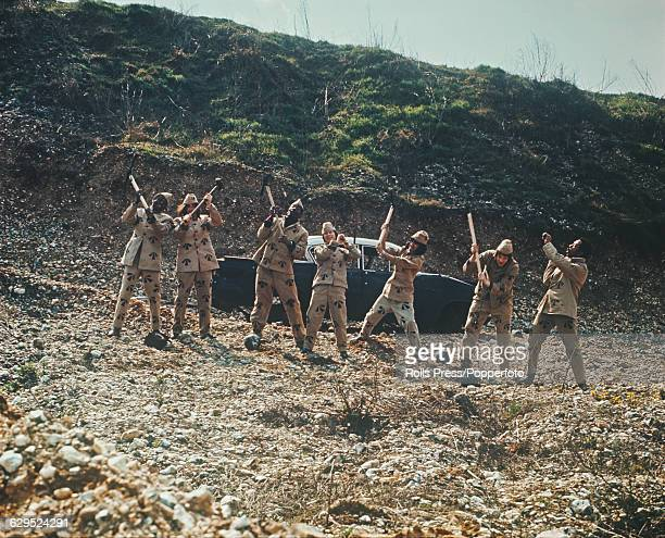 British soul and pop group The Foundations posed dressed as convicts wearing prison uniforms and holding sledgehammers whilst pretending to smash...